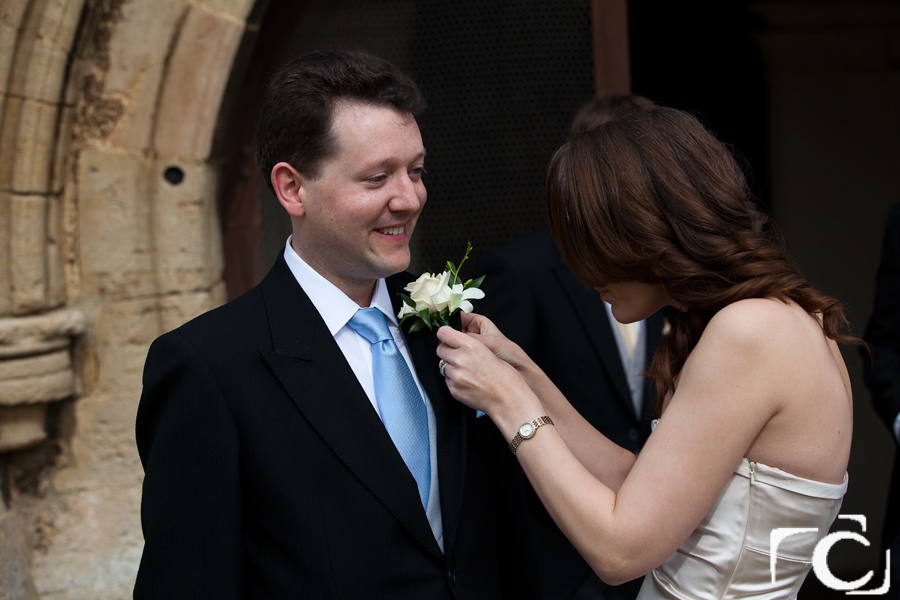 Bridesmaid helping the groom with his flower